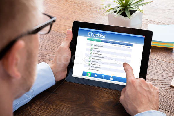 Businessperson Filling Checklist Form On Digital Tablet Stock photo © AndreyPopov