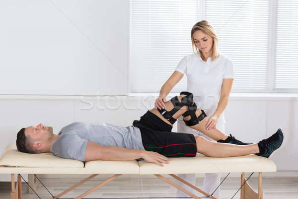 Female Physiotherapist Looking At A Man's Knee With Braces Stock photo © AndreyPopov