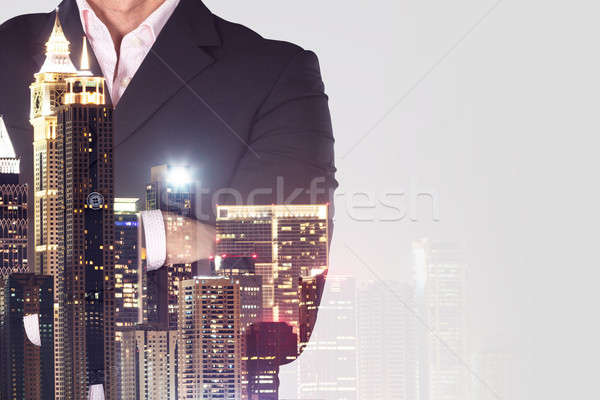 Businessman Standing Arms Crossed Over City Background Stock photo © AndreyPopov
