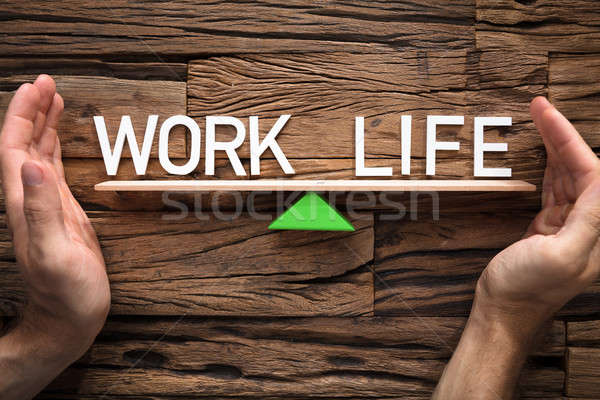Hands Covering Balance Between Life And Work On Seesaw Stock photo © AndreyPopov