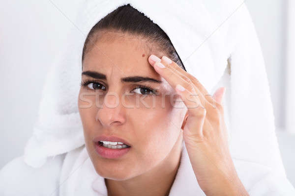 Young Woman Looking At Pimple And Squeezing Stock photo © AndreyPopov