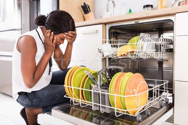 Sad Woman Crouching Near Dishwasher Stock photo © AndreyPopov