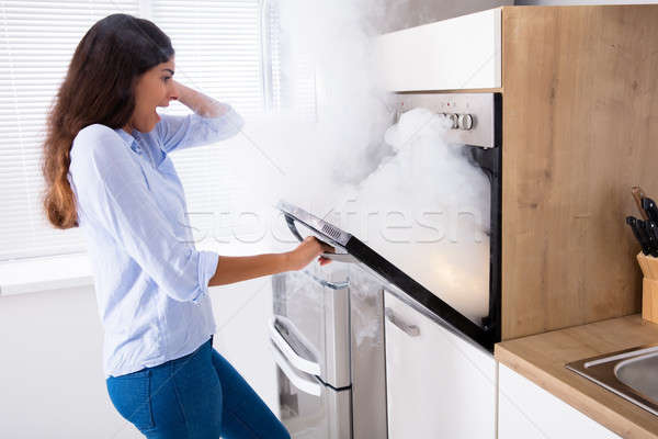Shocked Woman Looking At Smoke Coming From Oven Stock photo © AndreyPopov