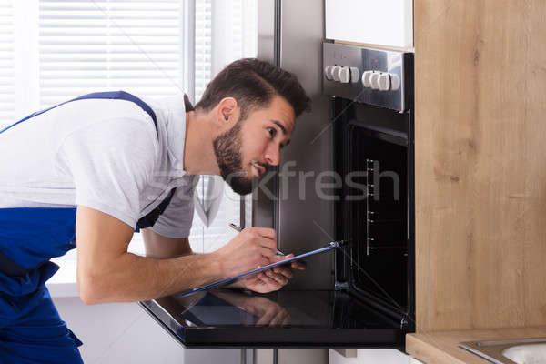 Elektricien schrijven naar oven jonge Stockfoto © AndreyPopov