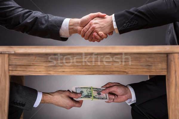 Stock photo: Businesspeople Shaking Hands And Taking Bribe Under Table