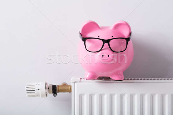 Thermostat And Piggy Bank With Eyeglasses On Radiator Stock photo © AndreyPopov