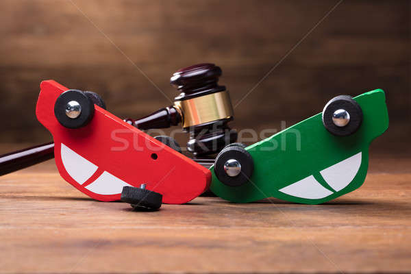 Collision Of Wooden Two Toy Cars In Front Of Gavel Stock photo © AndreyPopov