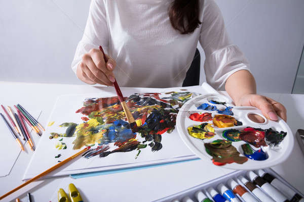 Artist Holding Paint Palette While Painting On Canvas Paper Stock photo © AndreyPopov