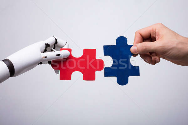 Robot And Human Hand Holding Jigsaw Puzzle Stock photo © AndreyPopov