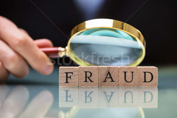 Businessperson Holding Magnifying Glass Over Fraud Blocks Stock photo © AndreyPopov
