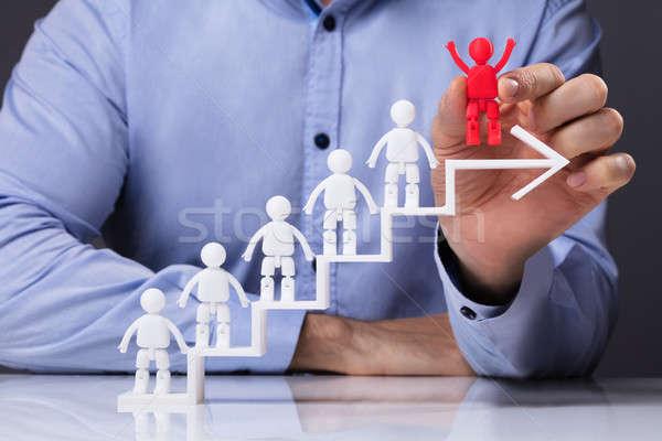 Man Placing Human Figure On Top Of White Arrow Stock photo © AndreyPopov