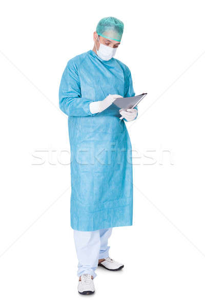 Doctor In Operation Gown Writing On Folder Stock photo © AndreyPopov