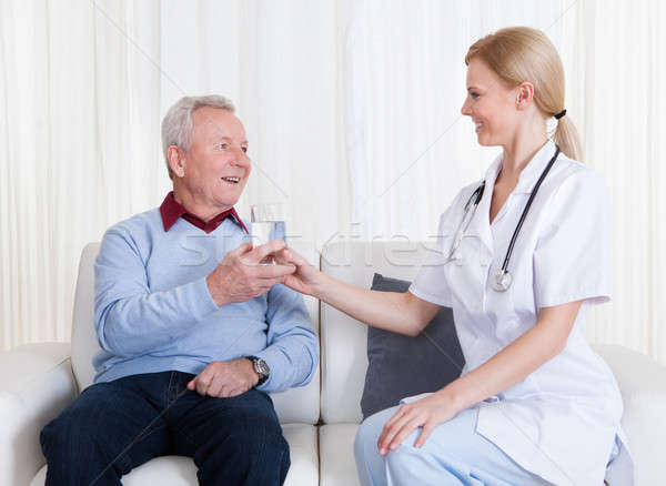 Caring Doctor Giving Water To Patient Stock photo © AndreyPopov