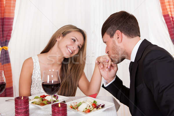 Man kissing a woman's hand at a romantic dinner Stock photo © AndreyPopov