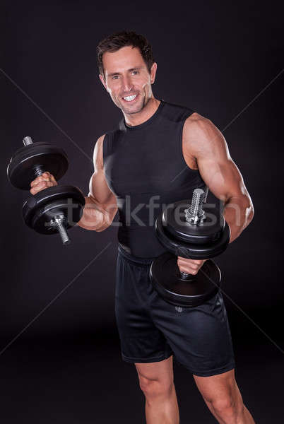 Young Attractive Man Pumping Weights Stock photo © AndreyPopov