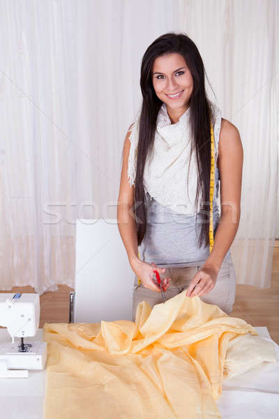 Beautiful woman cutting fabric Stock photo © AndreyPopov