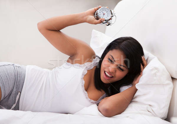Overslept Woman Looking At Alarm Clock Stock photo © AndreyPopov