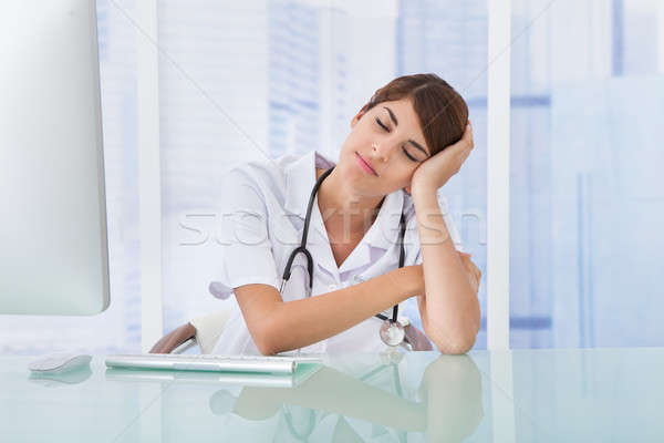 Tired Female Doctor At Desk Stock photo © AndreyPopov