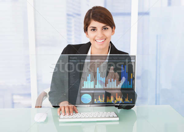 Happy Businesswoman Working On Graph At Computer Desk Stock photo © AndreyPopov