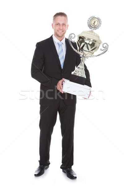 Stylish bearded businessman holding a large silver trophy Stock photo © AndreyPopov