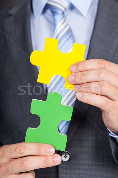 Stock photo: Businessman Joining Jigsaw Pieces
