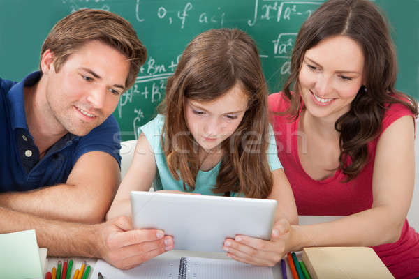 Smiling Parents Assisting Daughter In Using Digital Tablet Stock photo © AndreyPopov