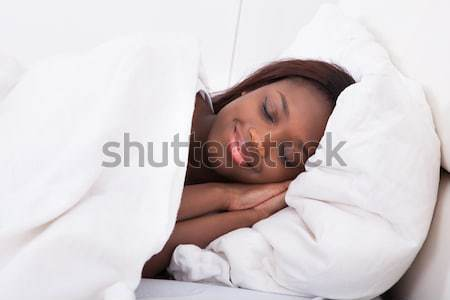 African American woman sleeping in bed Stock photo © AndreyPopov