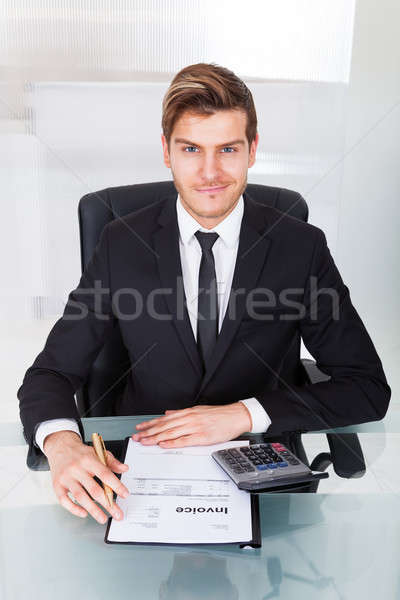 Businessman Checking Expenses At Office Desk Stock photo © AndreyPopov