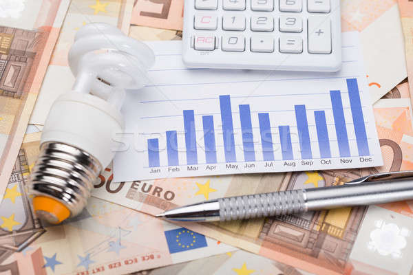 Bulb With Graph And Calculator On Euro Banknotes Stock photo © AndreyPopov