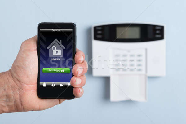 Person Holding Remote Control Of Security System Stock photo © AndreyPopov