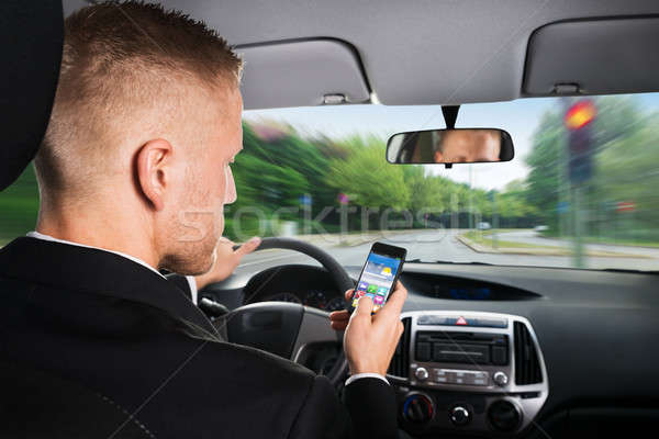 Businessman Using Cellphone While Driving A Car Stock photo © AndreyPopov