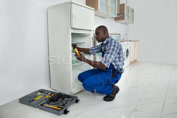 Fiatal szerelő javít hűtőszekrény afrikai konyha Stock fotó © AndreyPopov