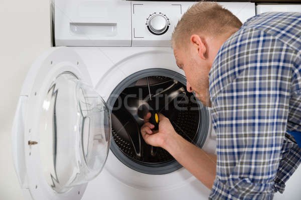 Trabalhador máquina de lavar roupa jovem global casa Foto stock © AndreyPopov