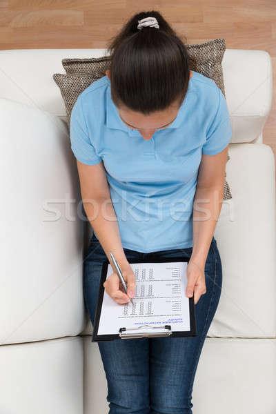 Nő kanapé tömés felmérés űrlap magasról fotózva Stock fotó © AndreyPopov
