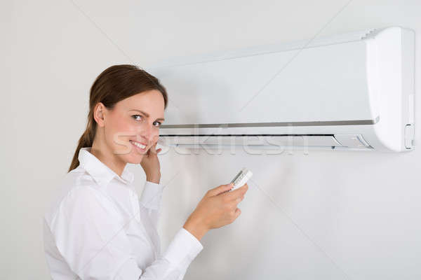Businesswoman Operating Air Conditioner Stock photo © AndreyPopov