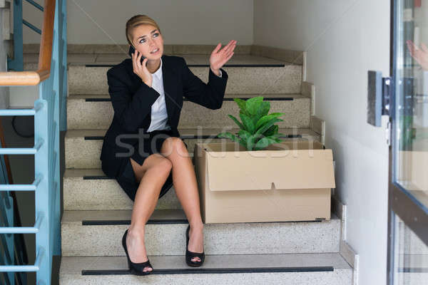 Fired Businesswoman Talking On Mobile Phone Stock photo © AndreyPopov