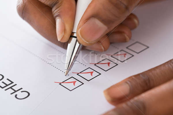 Person's Hand Marking On Checklist Form With Red Pen Stock photo © AndreyPopov