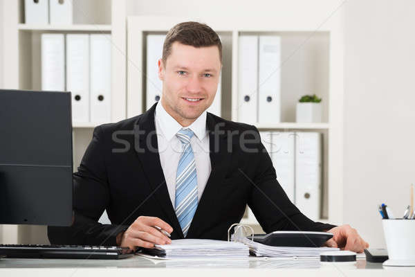 Confident Accountant With Calculator And Documents At Desk Stock photo © AndreyPopov