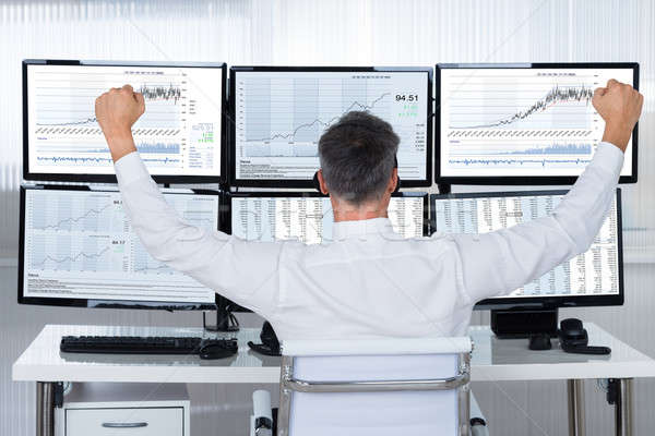 Successful Trader With Arms Raised Looking At Graphs On Screens Stock photo © AndreyPopov