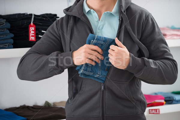 Man Hiding Jeans In Jacket At Store Stock photo © AndreyPopov