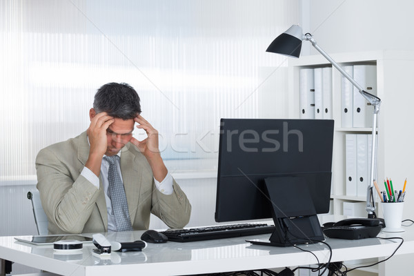 Mature Businessman Suffering From Headache At Desk Stock photo © AndreyPopov