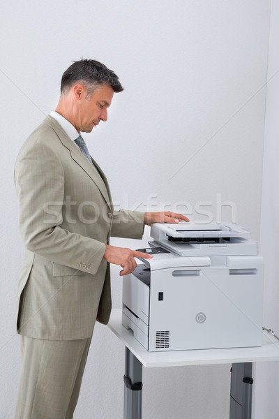 Businessman Keeping Paper On Photocopy Machine In Office Stock photo © AndreyPopov