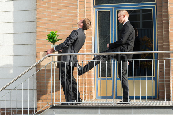 Businessman Kicking Employee With Belongings Outside Office Stock photo © AndreyPopov