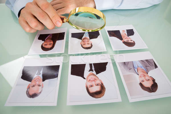 Person With Candidate Photograph And Magnifying Glass Stock photo © AndreyPopov