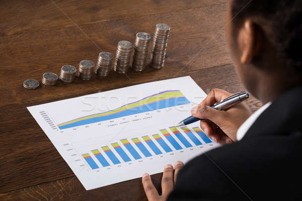 Businesswoman Analyzing Financial Graph With Coins On Desk Stock photo © AndreyPopov