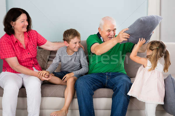 Grand-parent petits enfants bataille d'oreillers heureux grands-parents Photo stock © AndreyPopov