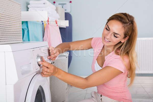 Mulher máquina de lavar roupa utilidade quarto jovem sorrindo Foto stock © AndreyPopov