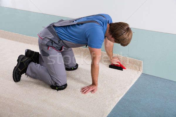 Stock photo: Male Craftsman Fitting Carpet