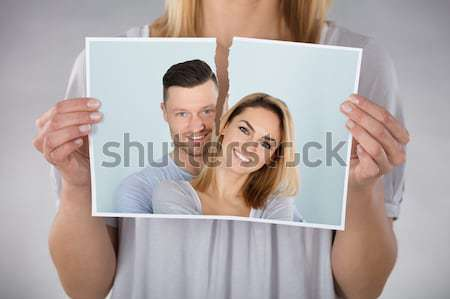 Woman Holding Torn Photo Stock photo © AndreyPopov