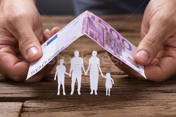 Hands Covering Family Under House Roof Made From Euro Note Stock photo © AndreyPopov